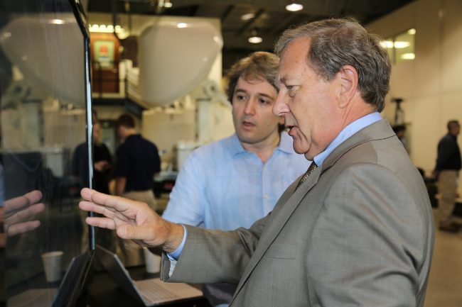 University of Iowa President Bruce Harreld (right) talks with Ibrahim Demir of the Iowa Flood Center about the Iowa Flood Information System (IFIS).