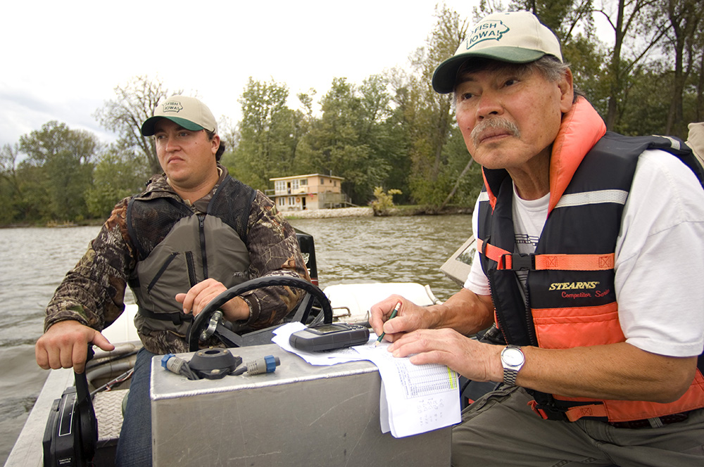 Tatsuaki Nakato (right) reintroducing endangered freshwater mussels into the Mississippi River near LACMRERS.