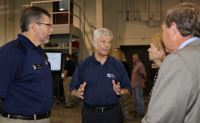 IFC Director Witold Krajewski (center) in conversation with UI President Bruce Harreld (right) and Mary Harreld. Dan Ceynar (left) looks on.