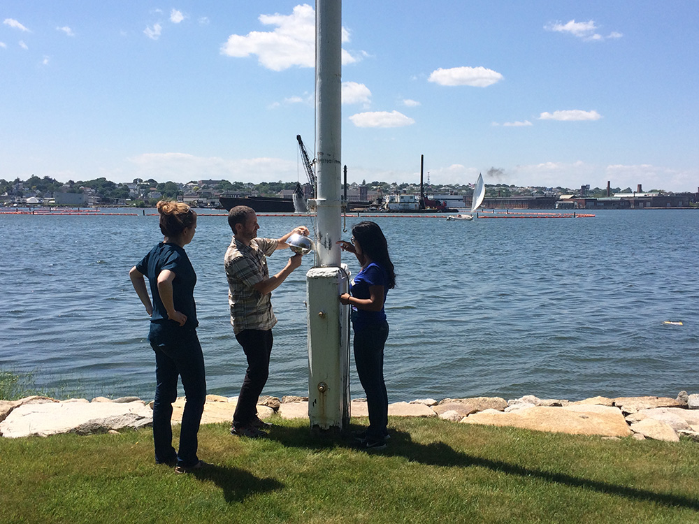 IIHR's Andres Martinez (center) adjusts a air passive sampler PCBs near the New Bedford Harbor in Massachusetts, while Kathryn Tomsho (left) and Komal Basra (right) from Boston University assist.