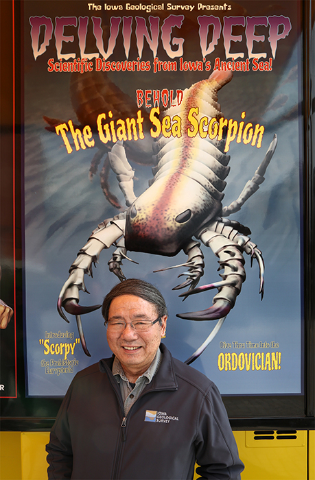 IGS researcher Paul Liu poses with the Mobile Museum sign that features a representation of the ancient sea scorpion fossil Liu and his colleagues discovered in northeast Iowa.