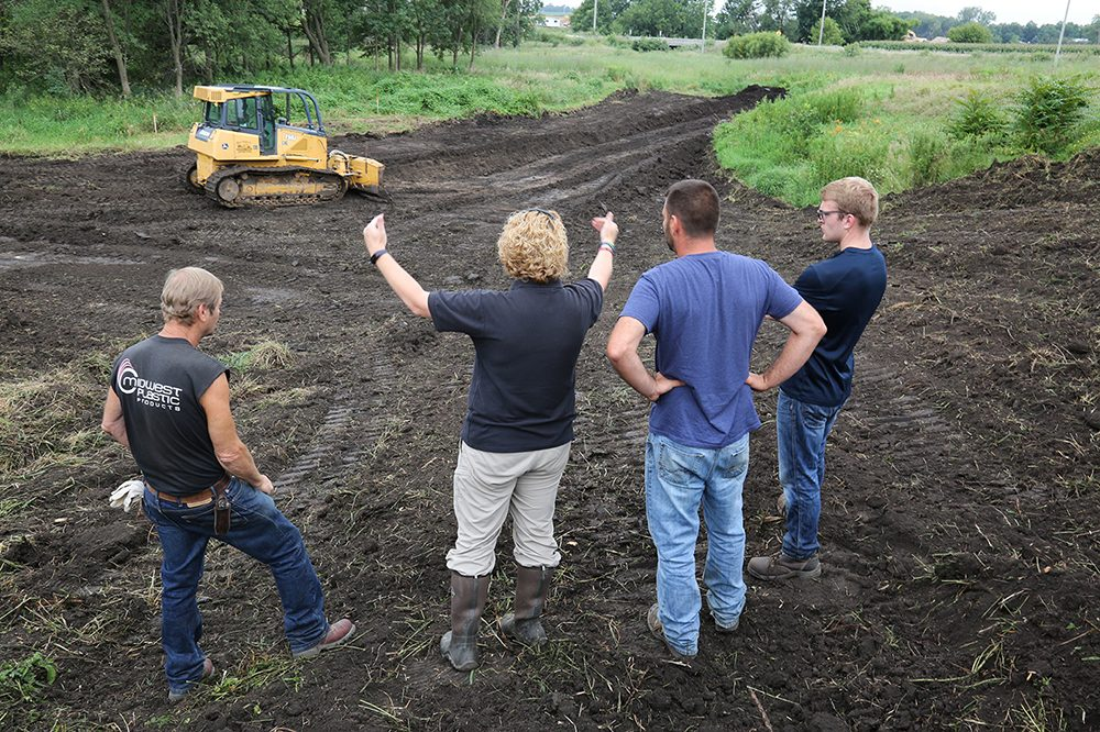 A bulldozer moves earth in the background as IIHR graduate students and U.S. Fish and Wildlife Service staff talk with staff of the earth-moving firm hired by Linn County.