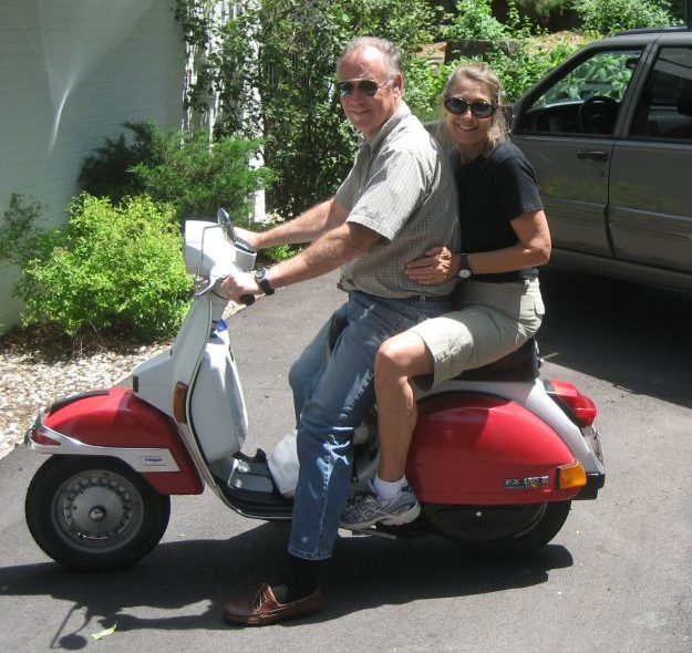 This is a candid snapshot of Forrest Holly and his wife Joyce riding a red and white Vespa scooter. They both look very happy.
