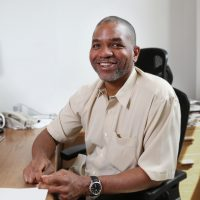 Eric Tate sitting at a desk, facing and smiling at the camera.