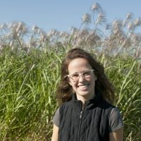 Luiza Notini stands in front of a miscanthus field, smiling and facing the camera.