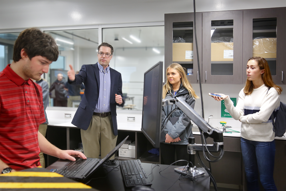 A faculty member, James Buchholz, points to a student working on a computer as reporters look on.