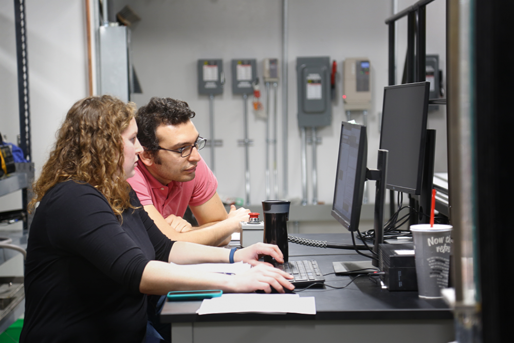 Two students, a man and a woman, look at a computer screen in the new Fluids Workshop.