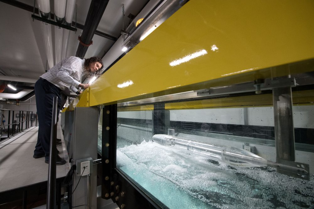 A male faculty member leans over to watch the flow of water through a flume in the Seamans Center Annex's new Fluids Workshop.