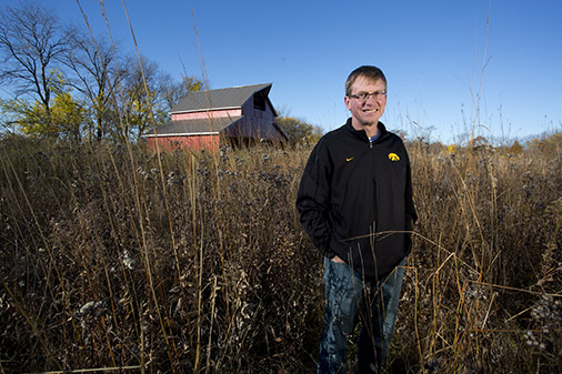 A man stands in front of a restored barn on a parcel of prairie.