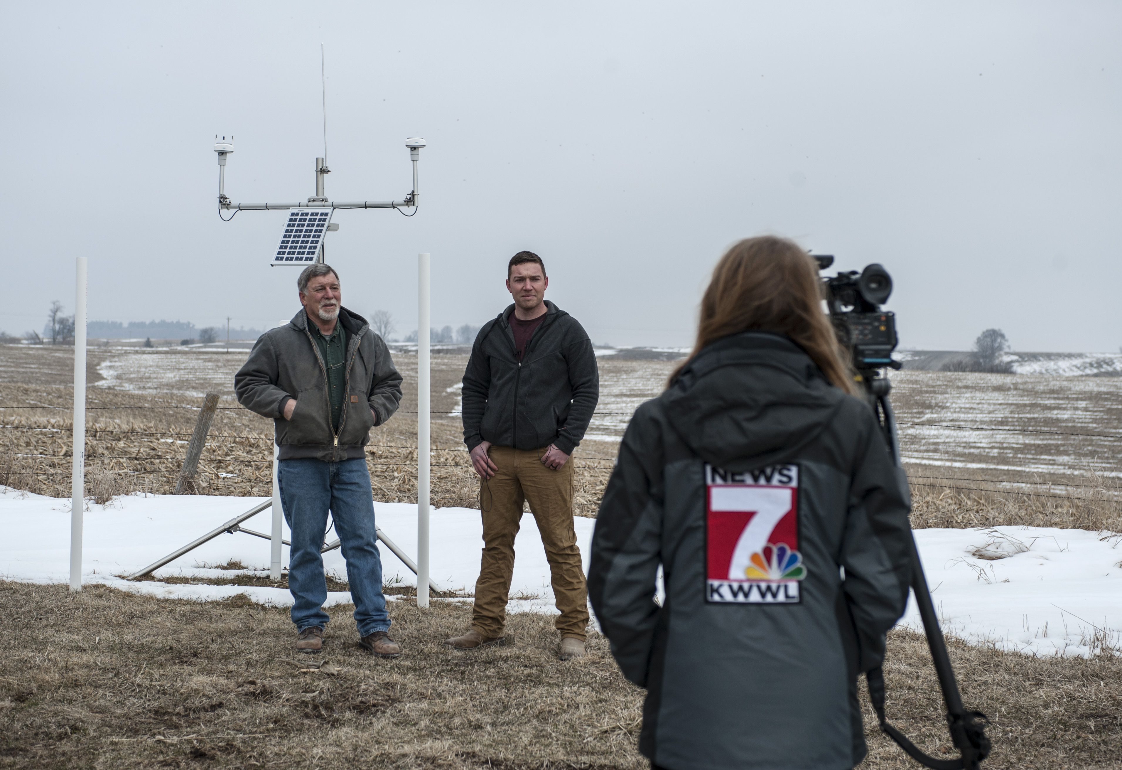 Two farmers stand in front of the tripod with the hydrologic instruments while a camera person from KWWL-TV films them.