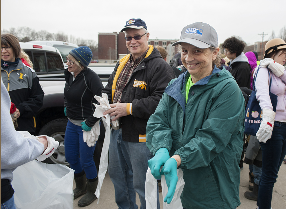 A crowd of people gets ready to participate in the river clean-up. In the foreground, a woman in a green jacket puts on green rubber gloves.