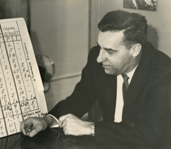 A vintage black and white photo of a man in a suit and tie working with a technical exhibit showing columns of numbers.