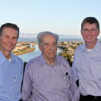 Three men pose in front of a river. They are (left to right) Jacob Odgaard, Rex Elder, and Larry Weber.