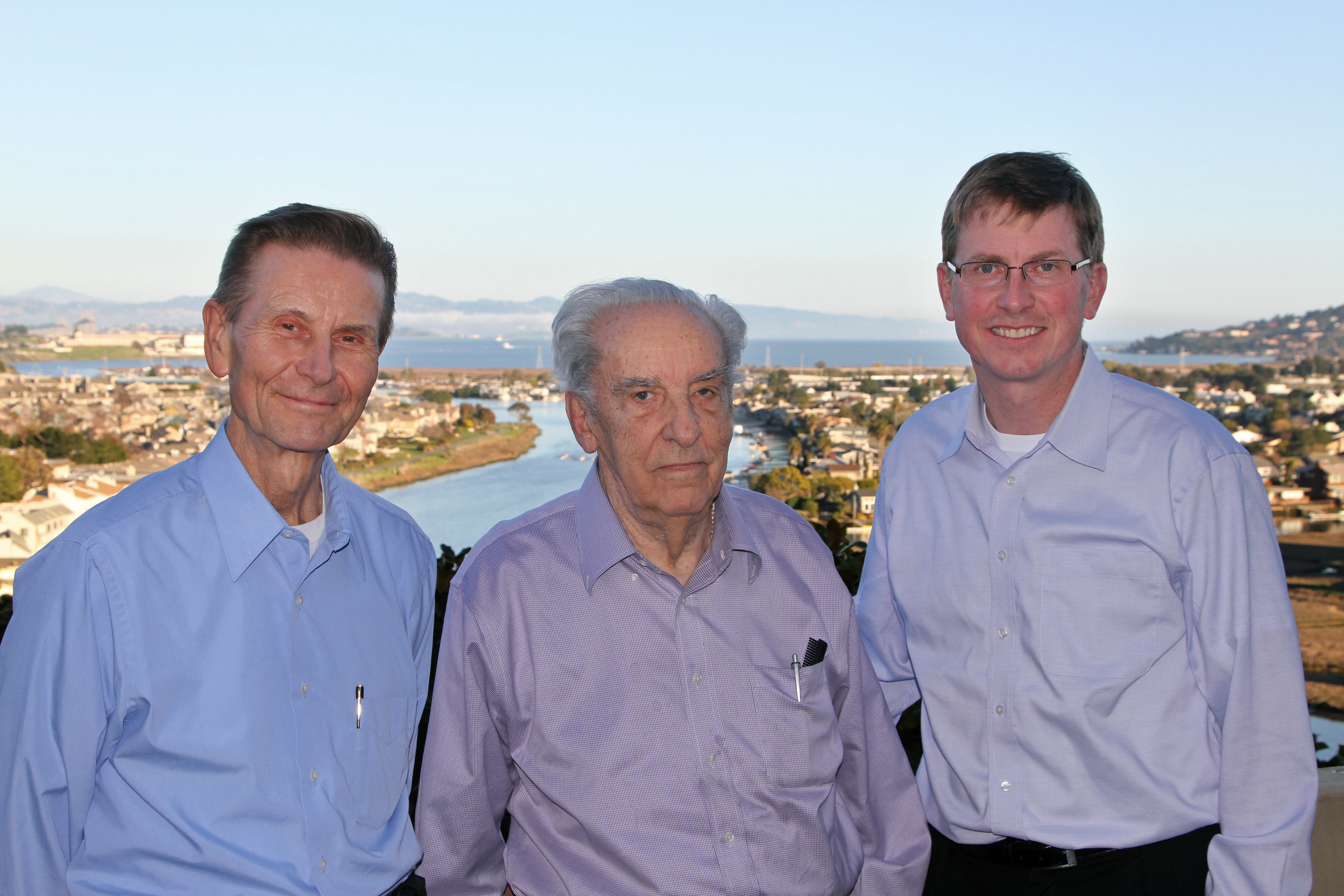 Rex Elder (center) poses with IIHR's Jacob Odgaard (left) and Larry Weber in front of a river and city.