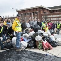 A big group of people poses with an impressive pile of trash.