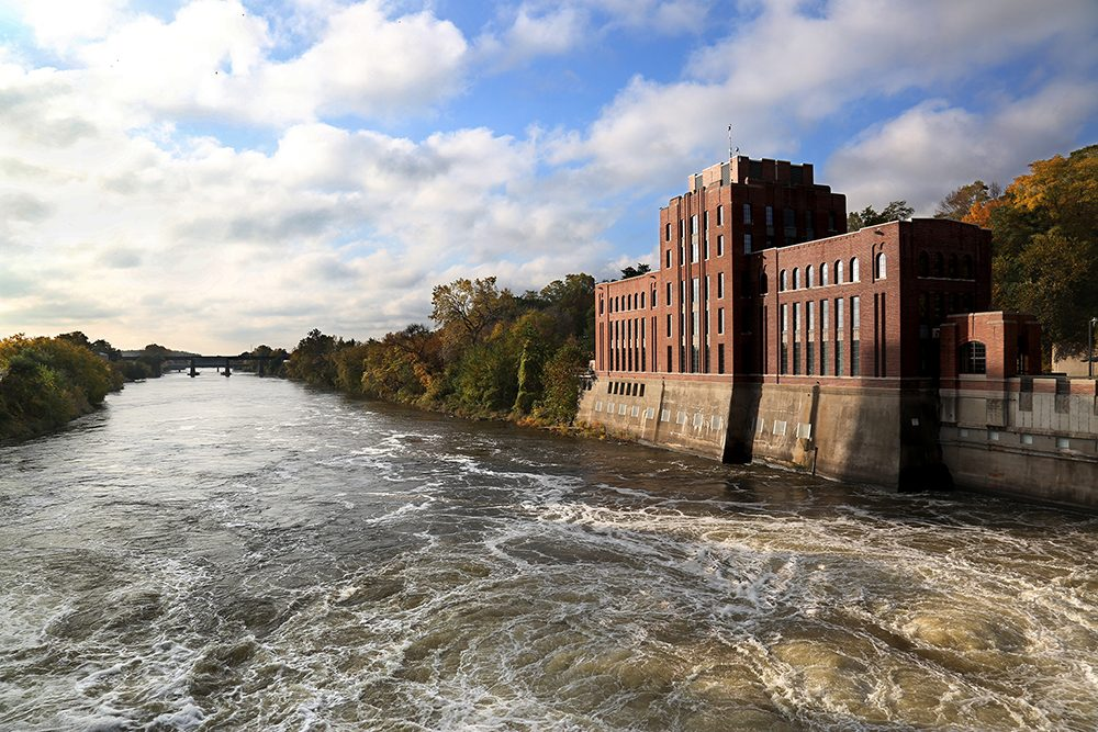 Five-story red brick building, Stanley Hydraulics Lab, set on the banks of the Iowa River in Iowa City.