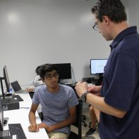 Faculty member James Buchholz talks with a high school student who participated in the SSTC program.