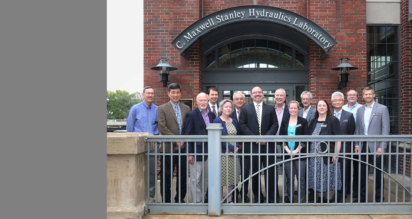 A group of men and women pose in front of the entrance to Stanley Hydraulics Lab.