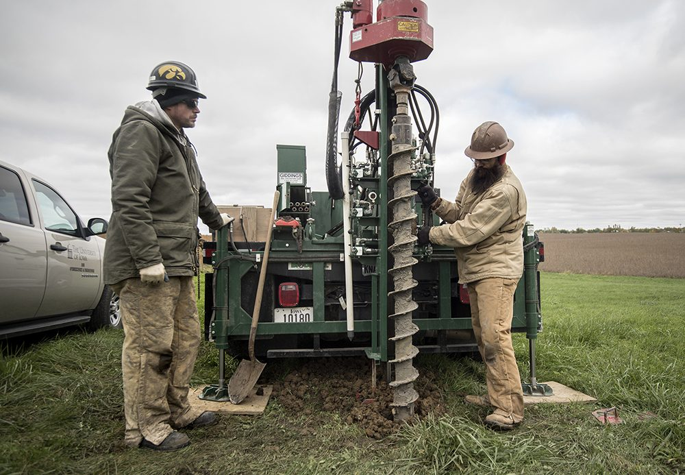 Two men in heavy cold weather clothing operate a drill rig attached to a pickup truck.