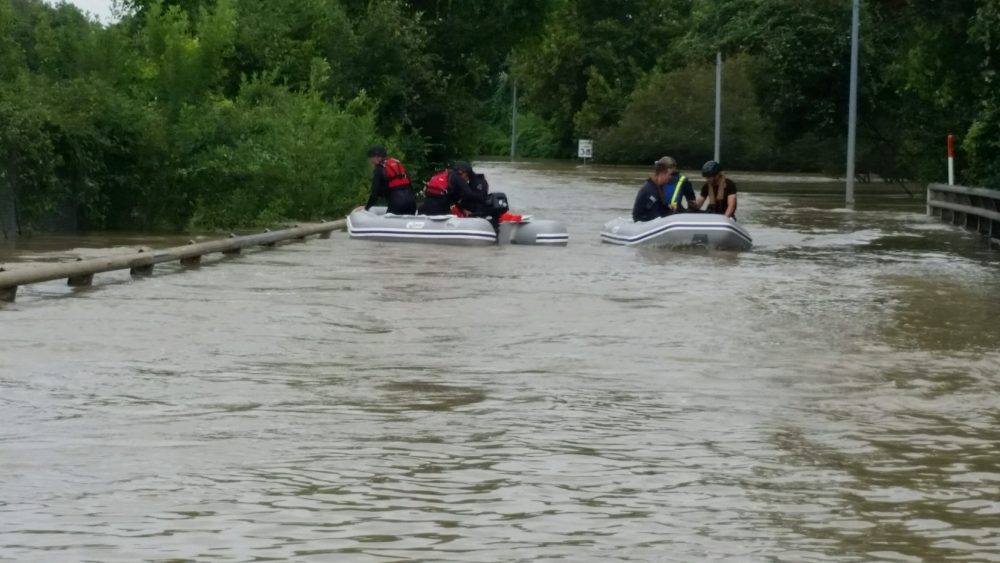 Two rescue boats navigate through floodwaters after Hurricane Harvey to rescue stranded residents.