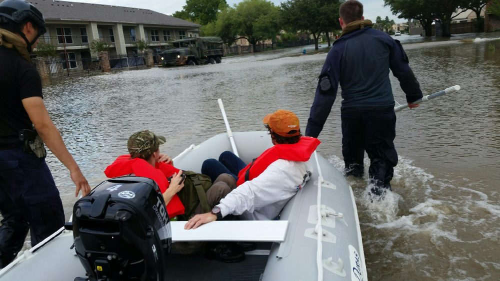 Two government officers guide an inflatable boat through floodwaters in Houston, Texas, after Hurricane Harvey.