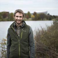 IIHR researcher Greg LeFevre stands near the Iowa River on the University of Iowa campus.