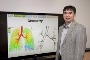 Professor Lin stands in front of an image of a lung