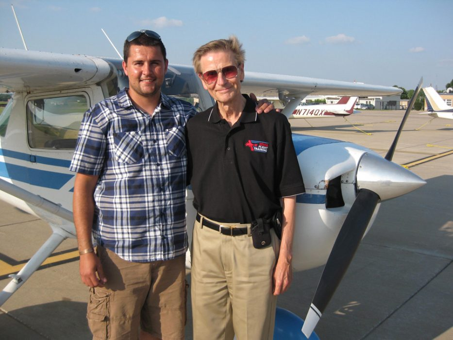 JAcob Odgaard and one of his flying students pose on the tarmac with a plane.