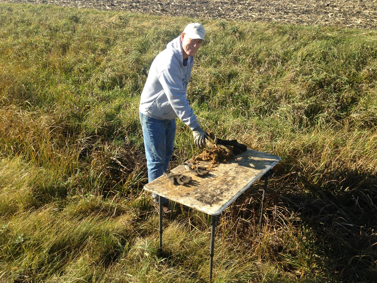 Keith Schilling stands in a road ditch examining soil samples on a table.