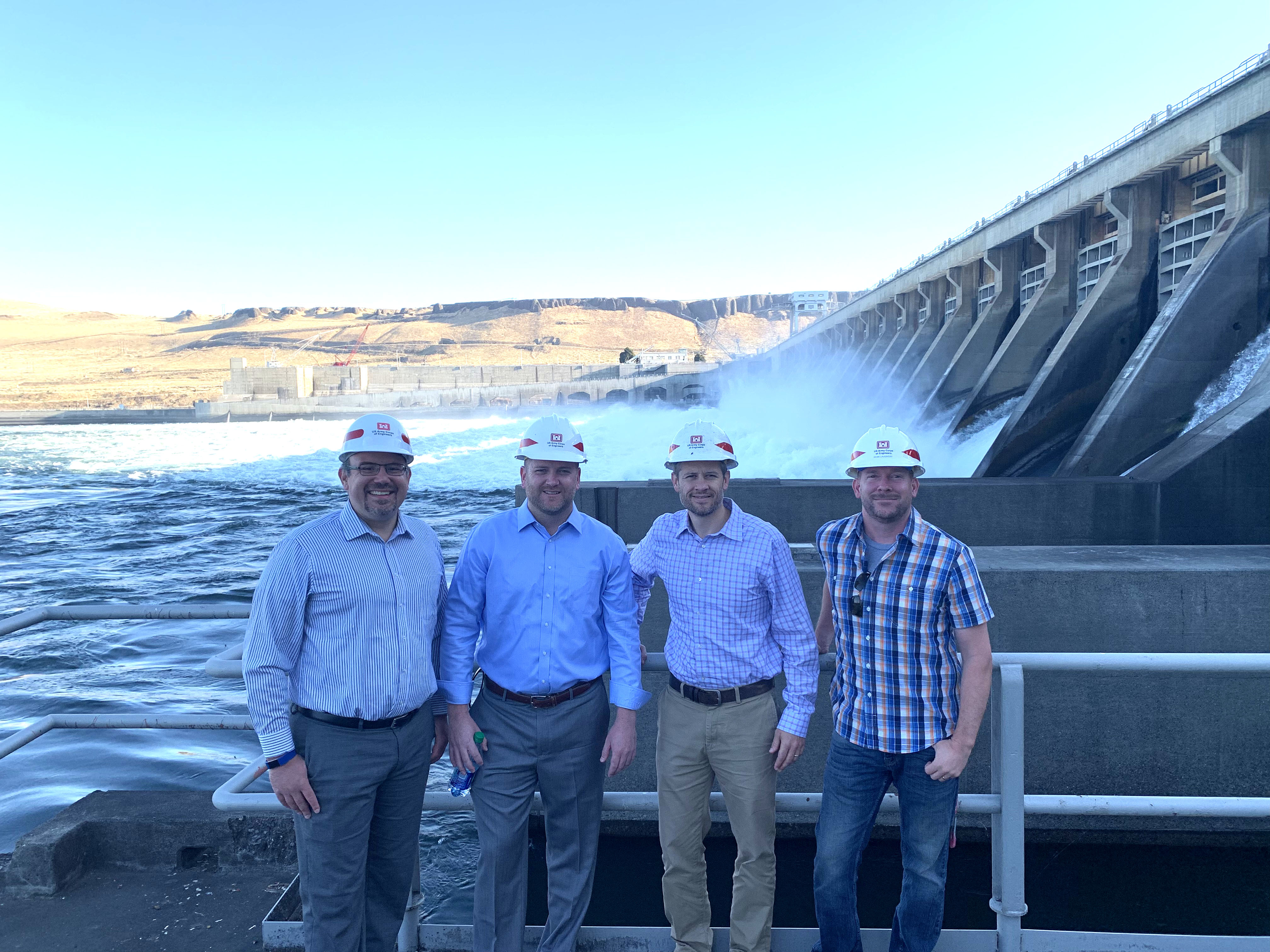 Four Men stand in front of a large dam