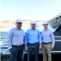 Three men stand in front of a large dam