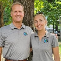 A man and woman in matching polo shirts pose under a tree.