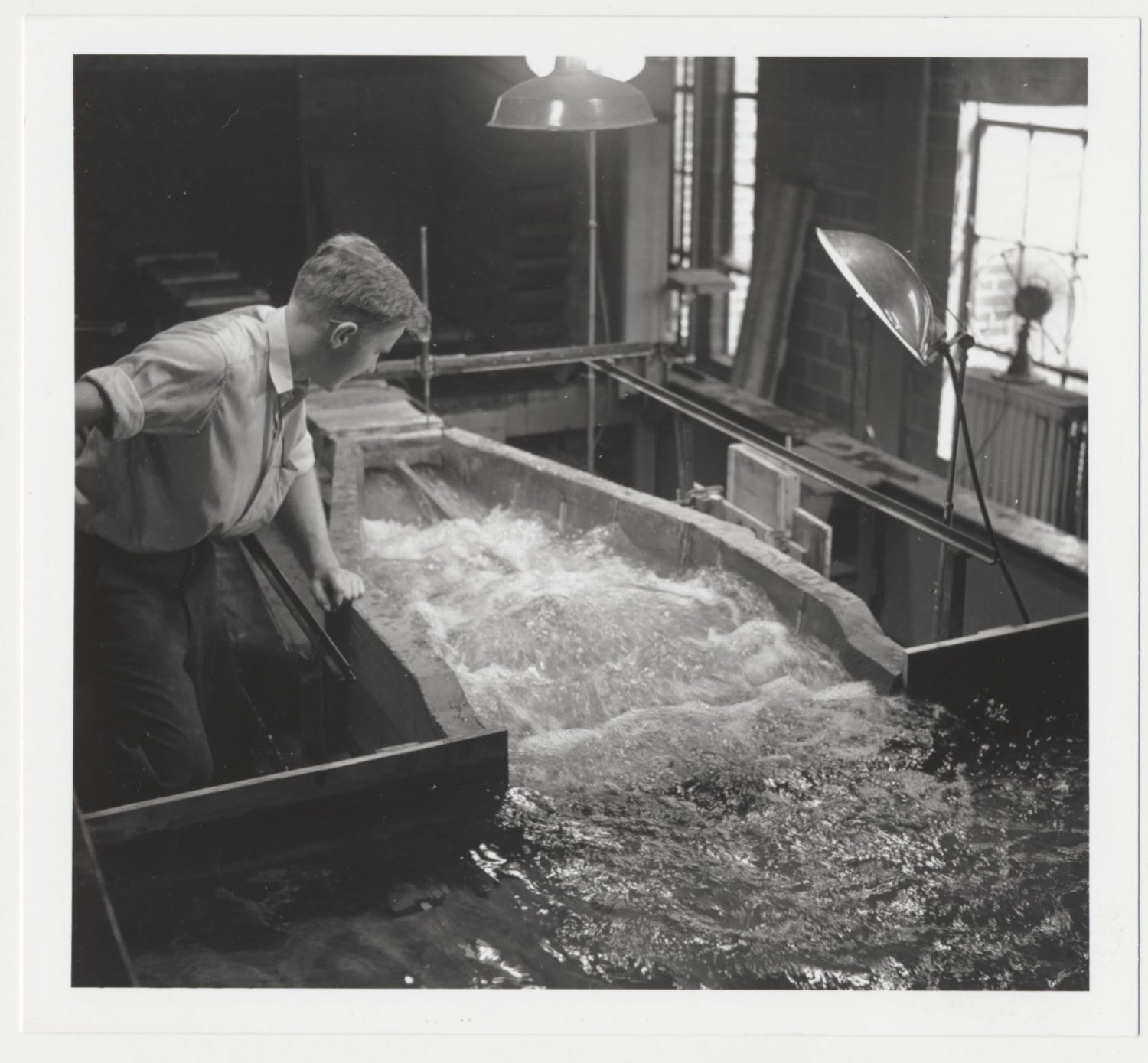 Black and white image of a student working with a flume in the 1940s.