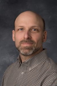 Professional headshot of Charles Stanier