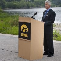 A man in suit and tie speaks at a podium outdoors on the riverbank