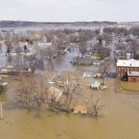 Aerial view of muddy brown floodwater submerging Pacific Junction, Iowa, in 2019.